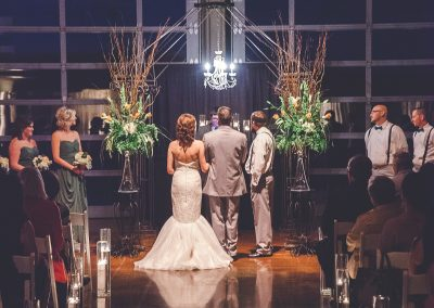 Wedding ceremony under arbor with chandelier